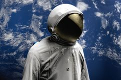 Astronaut on space mission flying around our blue planet. Earth on background. Cosmos. 3D render.  Stock Photos