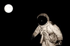 Astronaut in space with moon. An astronaut in suit and helmet in black space with the full moon in the background Royalty Free Stock Photo
