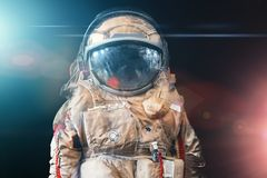 Astronaut or spaceman or cosmonaut on dark space background with blue and red light as sci-fi or fantastic explore background. For design royalty free stock photos
