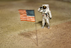 Astronaut or spaceman working on moon. Salute the USA flag Stock Image