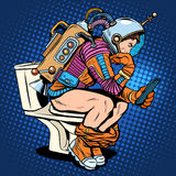 Astronaut thinker on the toilet reading a smartphone Stock Photos