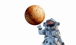 Touching the uniqueness. Mixed media. Astronaut touching with finger planet. Elements of this image furnished by NASA Stock Photo