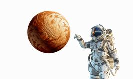 Touching the uniqueness. Mixed media. Astronaut touching with finger planet. Elements of this image furnished by NASA Stock Image