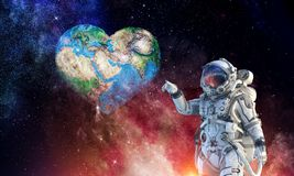 Touching the uniqueness. Mixed media. Astronaut touching with finger planet. Elements of this image furnished by NASA Royalty Free Stock Images