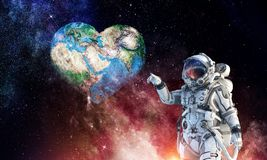 Touching the uniqueness. Mixed media. Astronaut touching with finger planet. Elements of this image furnished by NASA Stock Photos