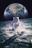 Astronaut walking on moon with earth in background. Elements of. This image furnished by NASA Royalty Free Stock Photo