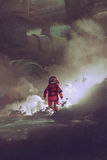 Astronaut walking through smoke on planet with sci-fi buildings on background Stock Photo