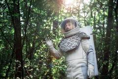 Astronauta assustado que localiza na floresta imagem de stock