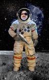 Astronauta con un arma que se coloca en el planeta Imagenes de archivo