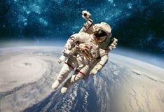 Astronauta en espacio exterior contra el contexto del eart del planeta imágenes de archivo libres de regalías
