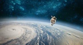 Astronauta en espacio exterior contra el contexto del eart del planeta imagen de archivo
