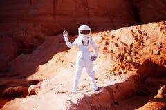 Astronauta futurista no planeta arenoso, acenando na câmera Imagem com efeito da tonificação Foto de Stock