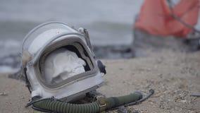 Astronauta muerto en el planeta El cráneo de la cabeza en el casco miente en la arena por el mar Preocupado accidentalmente almacen de metraje de vídeo