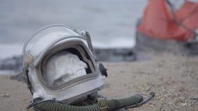 Astronauta muerto en el planeta El cráneo de la cabeza en el casco miente en la arena por el mar Preocupado accidentalmente metrajes