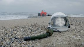 Astronauta muerto en el planeta El cráneo de la cabeza en el casco miente en la arena por el mar Preocupado accidentalmente almacen de video