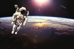 Astronaute dans l'espace extra-atmosphérique au-dessus de la terre pendant le coucher du soleil éléments Images stock