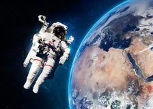 Astronaute dans l'espace extra-atmosphérique contre le contexte de Photos stock