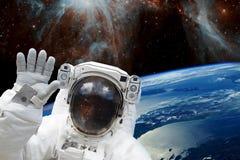 Astronaute dans l'espace extra-atmosphérique dans la combinaison spatiale contre de l'orbite bleue et l'espace de la terre Élémen photographie stock libre de droits