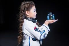 Astronaute de fille tenant l'usine photographie stock libre de droits