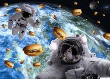 Astronautes dans l'espace extra-atmosph?rique avec des cheseburgers sur les plan?tes de la terre et de march?s sur le fond photo stock