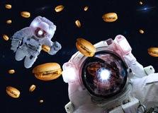 Astronautes dans l'espace extra-atmosph?rique avec des cheseburgers ?l?ments de cette image meubl?s par la NASA photos stock