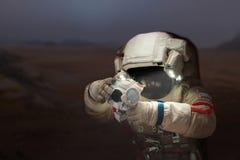 Astronautet med en kamera i en utrymmedräkt på planeten fördärvar royaltyfria bilder