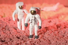 Astronauts. This is a picture of two astronauts figurines walking and discovering a planet with the space shuttle beheind Stock Photo