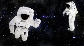 Astronauts in spacesuits floating in outer space. Spacemans at work. Starry dust. Elements of this image furnished by NASA royalty free stock photo