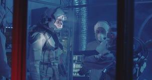 Astronauts testing spacesuit in laboratory