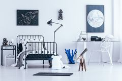 Astronomic bright bedroom interior. Astronomic posters on white wall in bright bedroom interior with telescope and white chair at desk near lamp and bed Royalty Free Stock Image