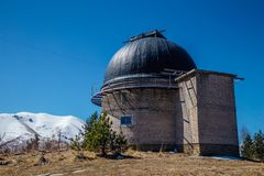 Astronomical observatory with telescope against the background of the blue sky and snowy peaks of the Caucasian mountains.  Royalty Free Stock Images