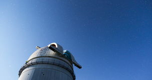 Astronomical Observatory under the night sky stars. Tilt. 4k. Rozhen astronomical observatory under the night sky stars. Blue sky with hundreds of stars of the stock video footage