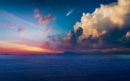 Bright comet in glowing sunset sky above dark blue sea Royalty Free Stock Images