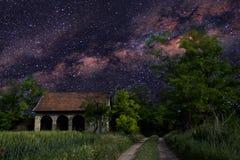 Astronomiephotographie mit kleinem Haus im Wald. Lizenzfreie Stockfotografie