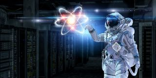 Astronomy as a science. Mixed media. Astronaut in suit touching atom molecule. Mixed media Stock Images