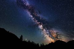 Astrophotography of Milky Way galaxy. Silhouette of mountains. Stars, nebula and stardust at night sky landscape stock photo