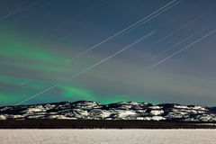 Star trails and Northern lights in moon lit night Stock Photo