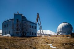 Astrophysical observatory in mountains on blue sky background at sunny day.  stock images