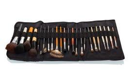 Astuccio per le matite nero con un insieme delle spazzole di trucco su bianco Fotografie Stock