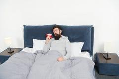 Astuces pour se réveiller tôt Lit somnolent barbu de visage d'homme avec le réveil dans le lit Quel bruit terrible Arrêtez cela photographie stock libre de droits