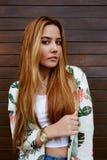 Asually-gekleideter weiblicher Hippie, der auf dem hölzernen Wandhintergrund schaut zu Ihnen steht stockfoto