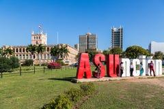 ASUNCION PARAGUAY - Juli 13, 2018: Fem turister poserar med den ASUncion bokstäver och presidentpalatset i bakgrund latin royaltyfri foto