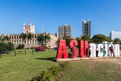 Five tourists are posing with ASUncion letters and Palacio de los Lopez (Presidential palace) in background. Asuncion, royalty free stock photo