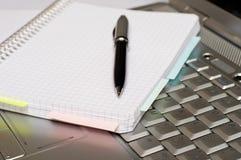 Asunto - tomar notas por una computadora portátil Fotografía de archivo libre de regalías