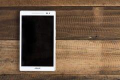 Asus品牌数字式片剂投入了木桌背景 免版税库存图片