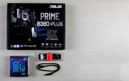 Asus moderkort i ask, processorn intel I3, RAM Kingston Fury Hyper 16 GB och kabel för förbindande apparater SATA 6Gbs på gråa lo royaltyfri bild