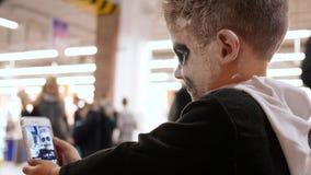 Asustadizo componga del esqueleto en la cara del muchacho para la celebración Halloween, niño hace la foto del selfie en el teléf metrajes