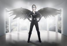 asustadizo la mujer se vistió en látex, azote y alas negras foto de archivo libre de regalías
