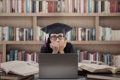 Asustado graduado del asiático del examen en la biblioteca Fotos de archivo libres de regalías