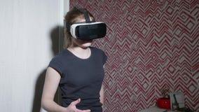 Asustan y están preocupada a la muchacha caucásica en los vidrios de VR que llevan detrás la camiseta La muchacha tiene miedo de  almacen de video